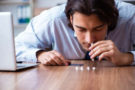 Young man having problems with narcotics at workplace Banco de Imagens