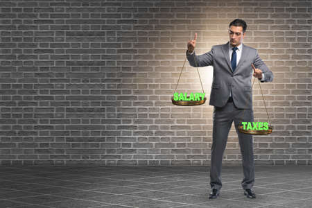 Businessman trying to find balance between taxes and salary Banco de Imagens - 131653707