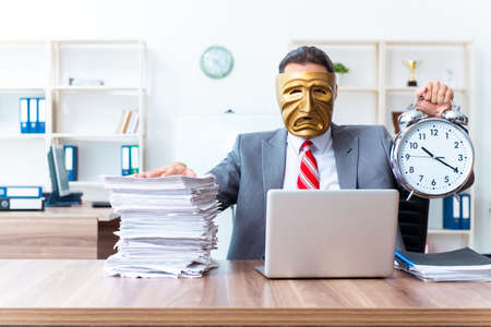 Businessman wearing mask in hypocrisy concept