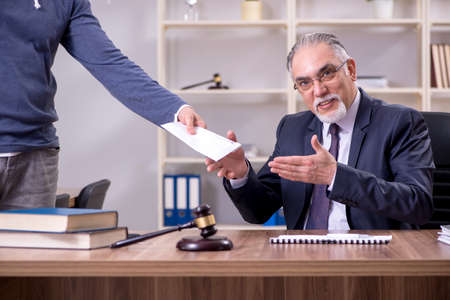 Old male lawyer in corruption concept