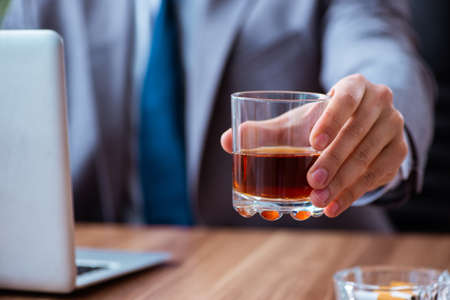 Male employee drinking alcohol and smoking cigarettes at workpla Stock Photo