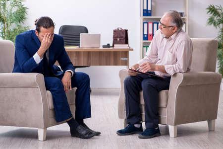 Young man visiting old male doctor psychologist Banco de Imagens