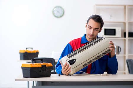 Young repairman repairing air-conditioner at warranty center