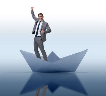 Excited businessman riding paper ship boat Banque d'images - 133006687