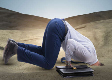 Businessman hiding his head in sand escaping from problems Reklamní fotografie