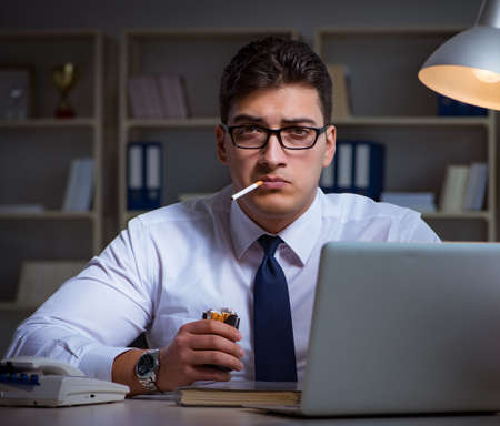 Businessman under stress smoking in office