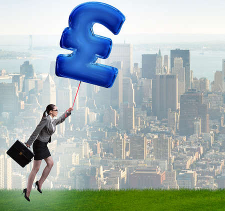 The businesswoman flying on british pound sign inflatable balloon