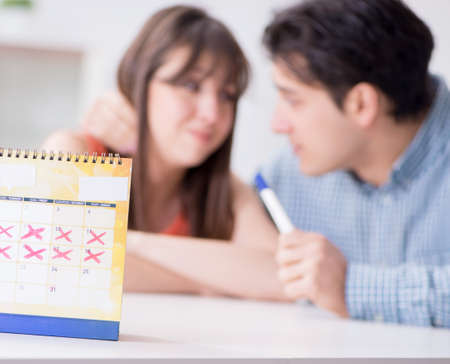 Young family in pregnancy planning concept with ovulation calender