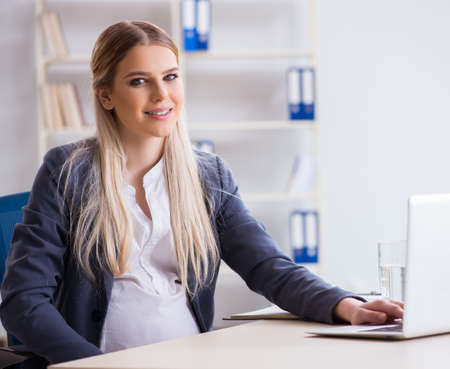 Pregnant woman employee in the office Stock Photo