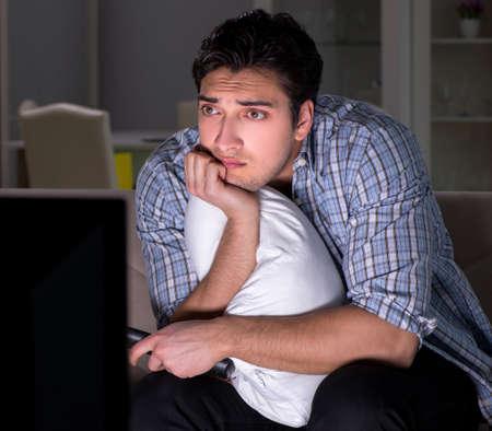 Young man watching tv late at night Stockfoto