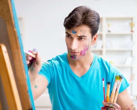 Junger lustiger Künstler, der an neuer Malerei in seinem Studio arbeitet