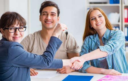 Jeune famille acceptant un contrat hypothécaire à la banque pour une nouvelle maison