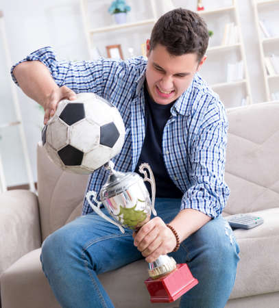 Young man student watching football at home Stockfoto