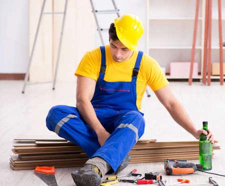 Floor repairman drinking alcohol during break