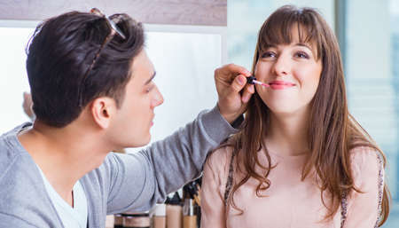 The man doing make-up for cute woman in beauty salon