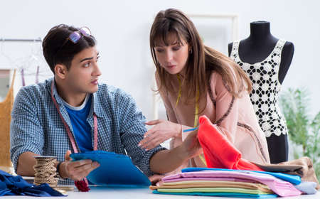 Male tailor with female student in workshop