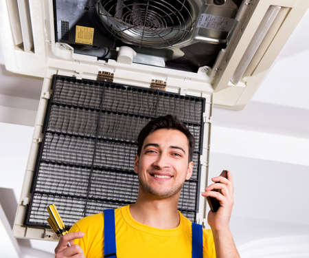 Repairman repairing ceiling air conditioning unit Stok Fotoğraf