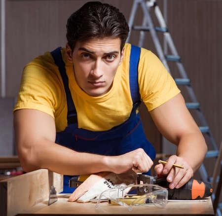 Worker working in repair workshop in woodworking concept Stock fotó