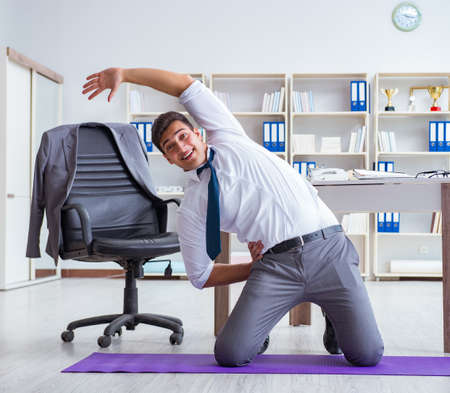 Businessman doing sports at his office space