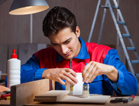 Young man gluing wood pieces together in DIY concept Stok Fotoğraf