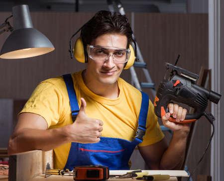 The worker working in repair workshop in woodworking concept Stock fotó