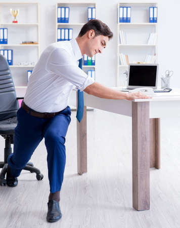 Young businessman doing sports stretching at workplace Stok Fotoğraf