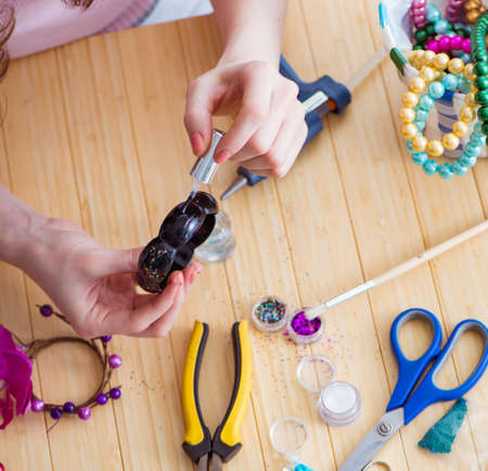 Woman making jewelry at home Stock Photo