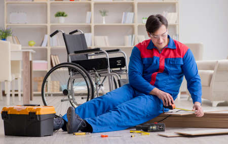 Disabled man laying floor laminate in office Stock fotó