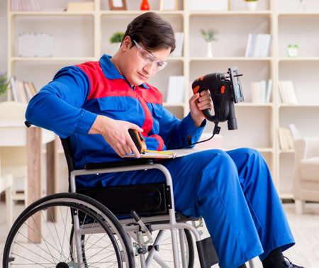 Disabled man working with handsaw at home Stock fotó