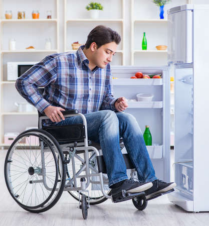 Young disabled injured man opening the fridge door 版權商用圖片