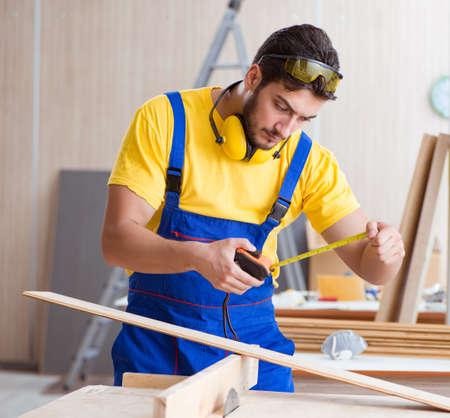 Young repairman carpenter working cutting wood on circular saw