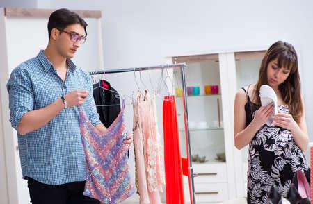 Ayudante de tienda que ayuda a la mujer con la opción de compra Foto de archivo