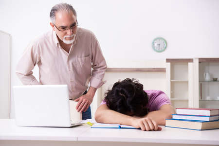 Old father helping his son in exam preparation Banque d'images