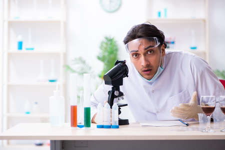 Male chemist examining wine samples at lab Stock Photo