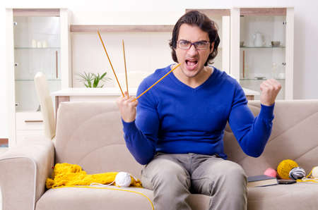 Young good looking man knitting at home Stock Photo