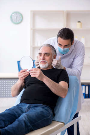 Old man visiting young doctor for plastic surgery Stock fotó