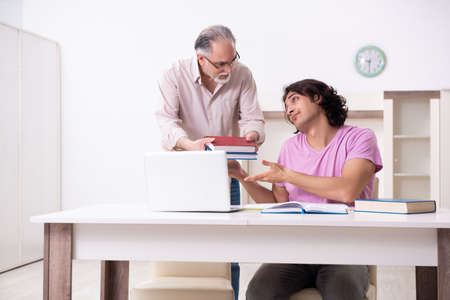 Old father helping his son in exam preparation Stok Fotoğraf
