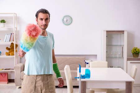 Giovane ferito che pulisce la casa
