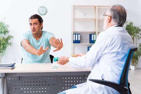 Young man visiting old male doctor