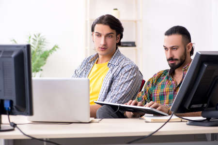 Two it specialists working in the office