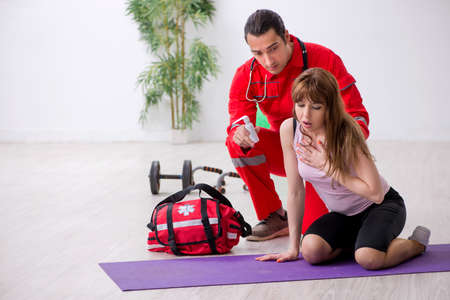 Paramedic in red visiting young woman in gym