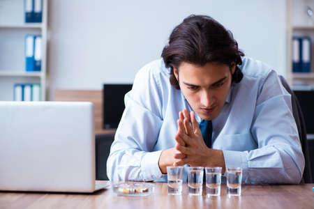 Male employee drinking vodka and smoking cigarettes at workplace