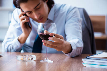 Male employee drinking alcohol and smoking cigarettes at workpla Standard-Bild
