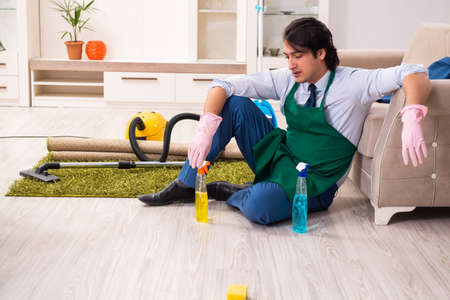Young businessman cleaning the house Archivio Fotografico