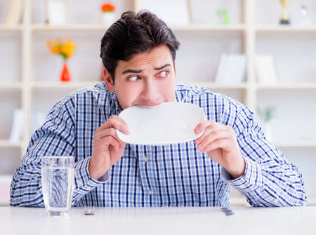 Man on diet waiting for food in restaurant Imagens