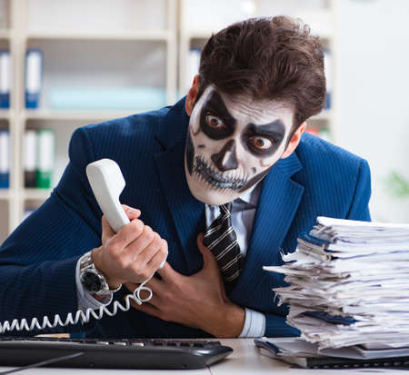 Businessmsn with scary face mask working in office 스톡 콘텐츠
