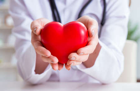 Doctor cardiologist with red heart in the hospital Stock fotó