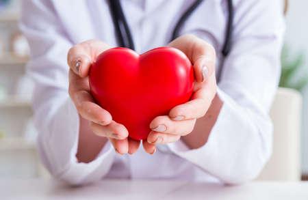 Médico cardiólogo con corazón rojo en el hospital Foto de archivo