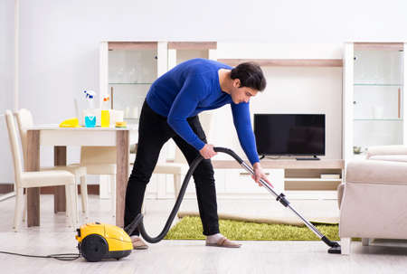Young man vacuum cleaning his apartment Imagens