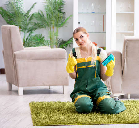 Professional female cleaner cleaning carpet